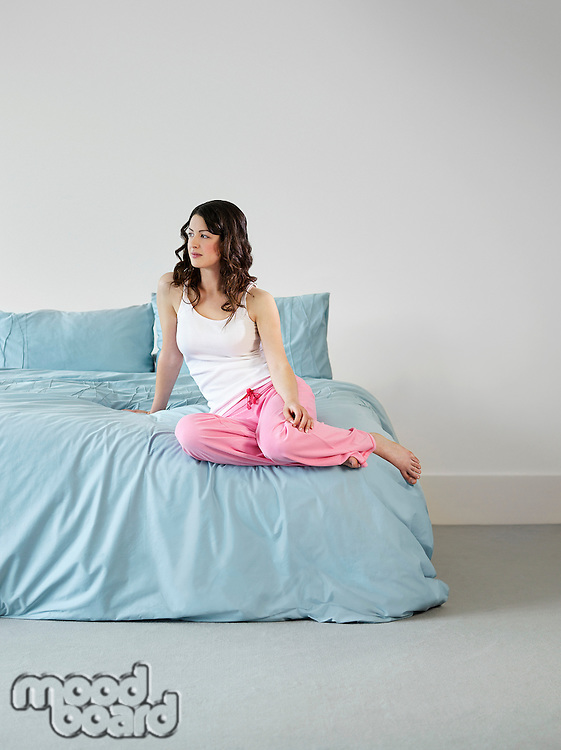 Young woman in nightwear sitting on bed