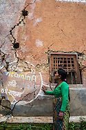 Kalpana Tamang (40), looks at the cracks in the partially collapsed house where she used to live with her 3 children in Kavre, Bagmati, Nepal on 30 June 2015.  Kalpana, a widow with 3 children, has been supported by SOS Children's Villages for many years now and had receive the Home-in-a-Box after the earthquake destroyed her house, almost killing her two daughters. She now lives in a temporary shelter, sharing her dwelling with farm animals, and is trying to make ends meet by weaving bamboo baskets to supplement the financial assistance provided by SOS Childrens Villages. The NGO mostly supports her children's welfare and schooling as well as provides her with essential household and schooling items like kitchen utensils and school books and uniforms. Photo by Suzanne Lee for SOS Children's Villages