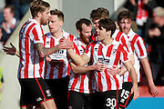 Dan Holman celebrates with his team mates after scoring for The Robins during the Vanarama National League match between Cheltenham Town and Boreham Wood at Whaddon Road, Cheltenham, England on 25 March 2016. Photo by Carl Hewlett
