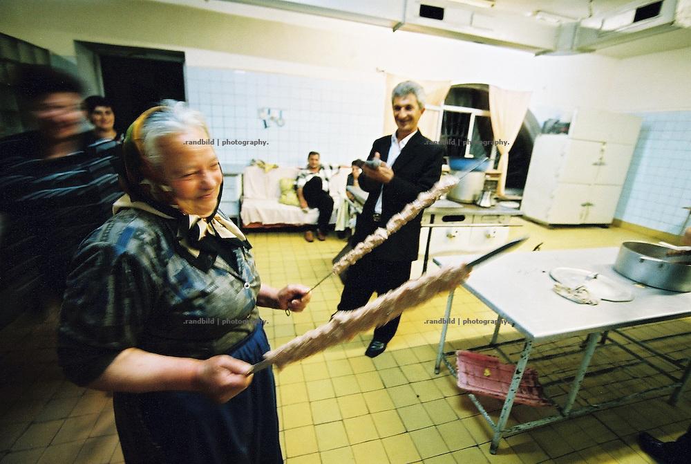 In den frühen Morgenstunden bringt diese alte Frau noch Kebab für den Grill in die Küche eines armenischen Restaurants. Armenische Feierlichkeiten gehen oft die ganze Nacht hindurch, was entsprechende Arbeit hinter den Kulissen nach sich zieht. An elder woman gets an applause for her traditional kebab in restaurant in Armenia.