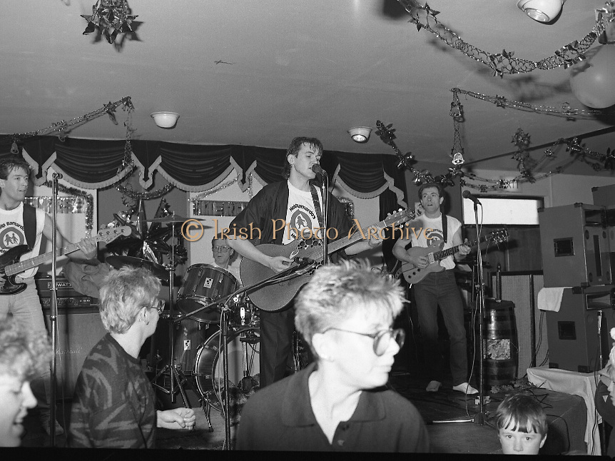 Christmas Party With Johnny Logan..1986..16.12.1986..12.16.1986..16th December 1986..At the 'Embankment',Tallaght, a charity Christmas Party was held for deprived children of the area. The main attraction was the singer and entertainer Johnny Logan,who with his band,entertained the children. Santa Claus took time off from his busy schedule to give a present to all the boys and girls. A great time was had by all...Picture shows Johnny Logan and his band, wearing their Barnardos tee shirts, entertaining the children. Barnardos organised the party for the deprived children of the area.