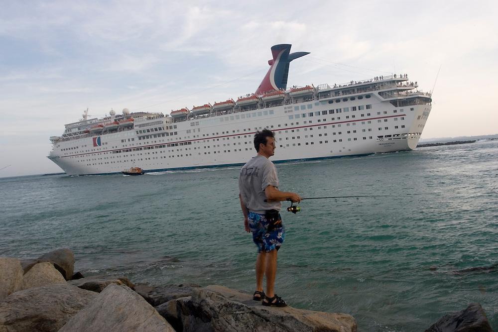 Un hombre pesca en South Point, al sur de Miami Beach, junto al dique por el que salen los cruceros del puerto de Miami.