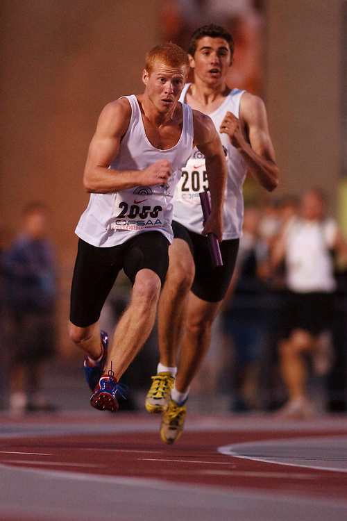 (London, Ontario}---09 June 2010) Alex Bahm of Thousand Islands (Brockville) receives the baton from Chris Cauley during the 4 X 100 meter relay heats at the 2010 OFSAA Ontario High School Track and Field Championships. Photograph copyright GEOFF ROBINS / Mundo Sport Images, 2010.