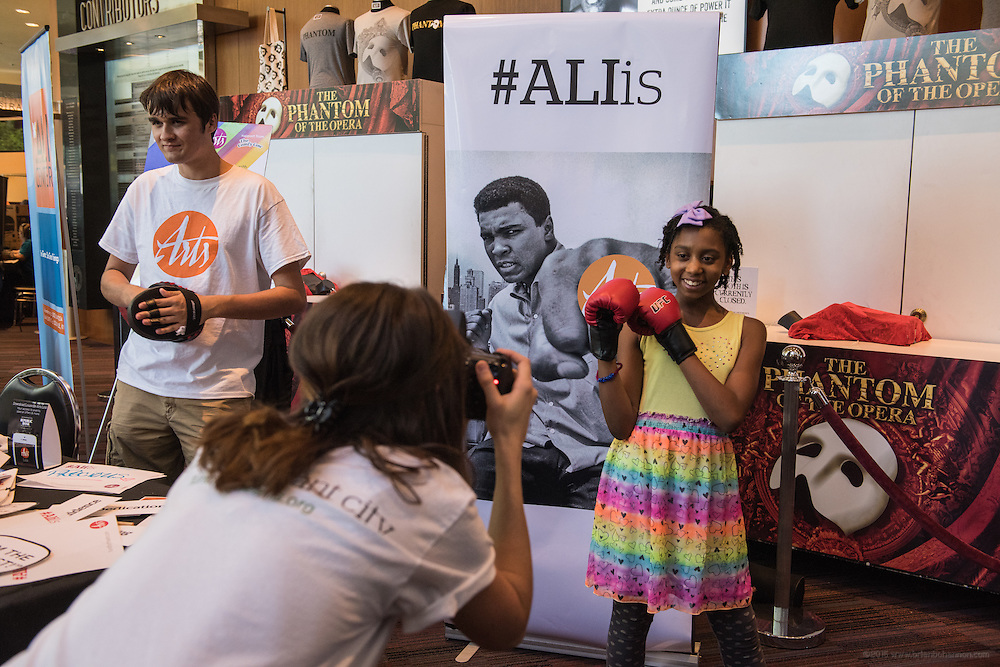 A mother photographs her daughter with fists up as booths from local arts and education organizations provide entertainment in the lobby of the Kentucky Center for the Performing Arts for the children-focused I Am Ali Festival, Wednesday, June 8, 2016, in Loiuisville, Ky. (Photo by Brian Bohannon)