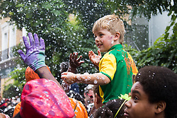 London, August 28th 2016. A little boy is showered with foam during Family Day at Europe's biggest street party, the Notting Hill Carnival.