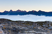 Valley fog settles between the Shuksan Arm and several mountains in the North Cascades on the border of Washington and British Columbia. Valley fog is caused by a temperature inversion. Heavier cold air gets trapped in valleys while warmer air passes above.