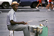 Co-Co-Mo-Jo and His Buckie Band;  a.k.a. Ko-Ko-Mo-Jo; performs on his home made drum set made from cans in Jackson Square; New Orleans, Louisiana circa 1983