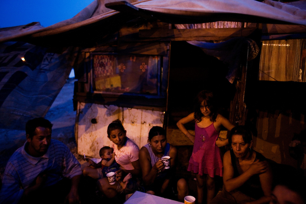 Stojan's family and friends outside the front door to their home at dusk, Nova Gazela camp.