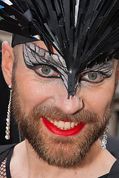 London, June 28th 2014. Dressed in drag, a bearded reveler gazes into the camera as the Pride London parade proceeds through the city's streets.