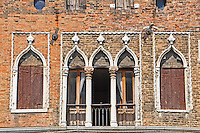 Detail of a beautiful old Venetian brick house facade including shapely doors and windows.