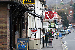 © Licensed to London News Pictures. 27/01/2012. Wendover, UK. An elderly woman walks past an ant HS2 (High Speed Rail 2) sign in he town of Wendover, Buckinghamshire. Scheduled to be completed by 2033, the new Rail system will have huge effects on the traditional English town. Photo credit : Ben Cawthra/LNP