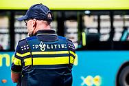 AMSTERDAM - Politie op straat in Amsterdam , survieren ,  op de fiets , fietsen , verkeersregelaar , bellen , telefoon ,