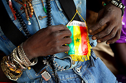 DAKAR, Sept. 5, 2011  A soccer enthusiast shows the flag of Senegal's national soccer team in Dakar, capital of Senegal, on Aug. 24, 2011. .In Senegal, located on the western tip of the African continent, there must be soccer enthusiasts if there is an open area, no matter dawn or dusk, sunny or rainy. Senegalese boys begin to play soccer since five or six years old in their childhood. Although most of them have no opportunity to wear a pair of professional plimsoll or to play soccer on a professional field, their love for soccer can not be stopped by anything. .Senegal started amateur soccer league matches from 1960, and there was no professional league match until 2009. However, based on the people's enthusiasm for soccer, Senegal's national soccer team has entered the final eight of the World Cup 2002 and has won the champion of Africa Cup of Nations. .A great number of Senegalese soccer talents have emerged in Senegalese history, among whom there are also some big stars who play in professional leagues overseas. The former Arsenal captain Patrick Vieira was born in Dakar. Manchester United striker El Hadji Diouf is also Senegalese. .Senegalese soccer stars fulfilled their achievements and have become the heroes in local children's eyes. Palmer,  once a soccer player in professional leagues of Saudi Arabia, works as a soccer coach now. In Palmer's mind, it is true that some boys dream to become professional soccer players to change their own impoverished destiny. However, soccer's popularity in Senegal is more related with the love for soccer from the bottom of people's heart. Playing soccer does not need costly outfit and no matter you are rich or poor, all the players in the soccer field are equal with each other and could harvest endless happiness from the sport. (Credit Image: © Xinhua via ZUMA Wire)