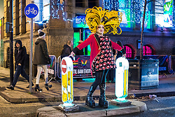 "© Licensed to London News Pictures . 15/12/2017. Manchester, UK. A club promoter wearing drag hands out flyers on Sackville Street in Manchester's "" Gay Village "" . Revellers out in Manchester City Centre overnight during "" Mad Friday "" , named for historically being one of the busiest nights of the year for the emergency services in the UK . Photo credit: Joel Goodman/LNP"
