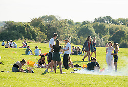 """© Licensed to London News Pictures; 14/09/2020; Bristol, UK. Groups of people, some more than six in number, enjoy the sunshine and hot weather on Bristol Downs. From today Monday 14 September it is illegal to meet up socially in groups of more than six people, known as the """"Rule of Six"""", in order to try and contain the spread of the covid-19 coronavirus pandemic, and police have said they will enforce the law with fixed penalty notices which will increase for repeat offenders. There are some exceptions to the new law such as larger families that live together or if a support bubble is greater than six. People should still practice social distance if they do not live in the same house hold or support bubble. Bristol recently recorded the biggest daily increase in 10 weeks of new cases of coronavirus, and nationally, 3,539 new cases have been confirmed, the highest rise for four months. Photo credit: Simon Chapman/LNP."""