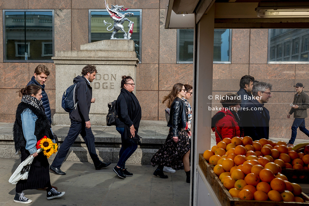 A lady carries a single sunflower past fresh oranges on sale at a stall on London Bridge during the evening rush-hour, from the City southwards to Southwark, on 3rd May, in London, England
