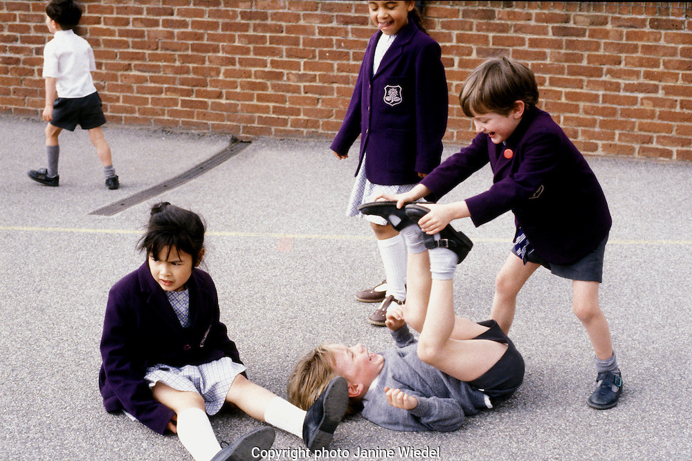 Primary children playing roughly at school recess time in  playground of South London school.