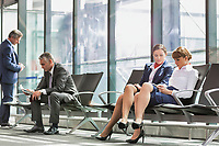 Businesss people sitting while waiting for boarding in airport