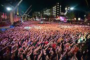 La foule, littéralement en transe, fait la vague devant la grande scène à la fin du spectacle hommage aux Colocs lors des Francofolies de 2009.