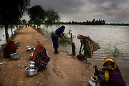 Flood displaced women fetch water from a pump next to rising flood waters, on 10 September, 2011, in Fatehpur, Pakistan. More than 17% of children in the flood areas are severely acutely malnourished and 67% of livestock has been destroyed after torrential monsoon rains, reminiscent of the 2010 floods that devastated Pakistan, have reportedly already killed over 200 people, left 300,000 homeless and affected over 7 million. (Photo by Warrick Page)