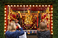 © Licensed to London News Pictures. 21/12/2017. London, UK. Shoppers admire the Christmas window displays at Selfridges on Oxford Street in central London on 'Panic Thursday', shortly before Christmas. Retailers are expecting an extremely busy day. Photo credit: Rob Pinney/LNP