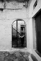 """""""Salento on Street"""".e? un lavoro fotografico che ha come oggetto scene quotidiane, che avvengono in strada o in luoghi pubblici salentini...una donna osserva fuori dal portone di casa"""