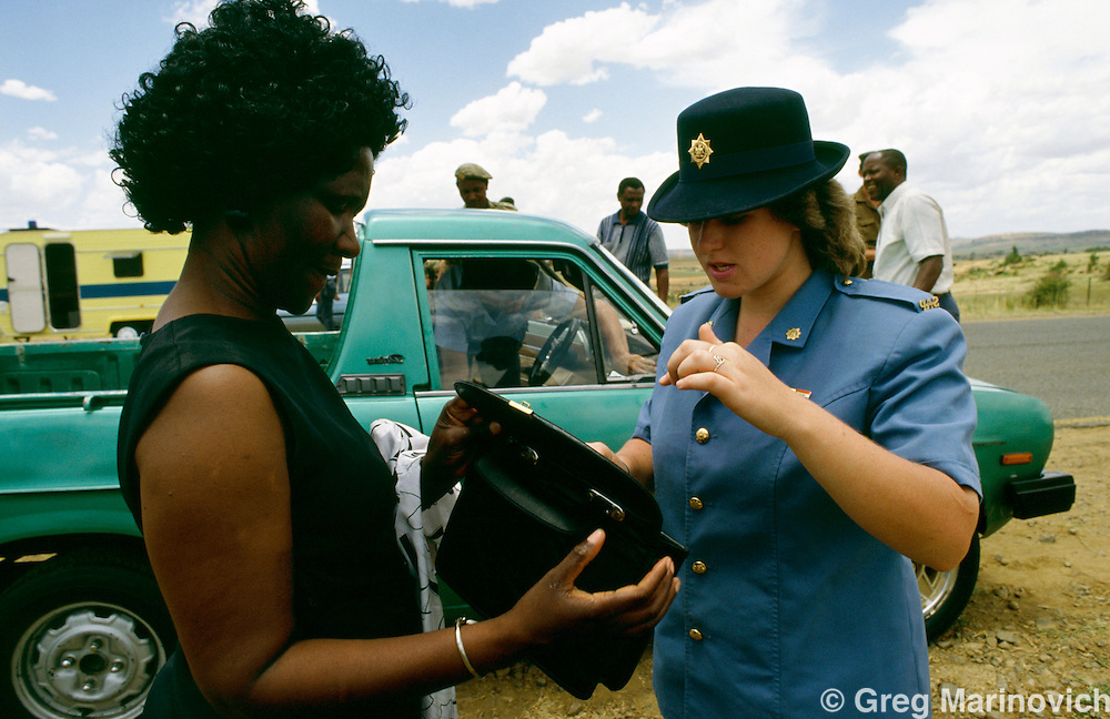Orange Free State, South Africa, 1994. A policewoman checks a woman's handbag at a roadblock in the OFS.