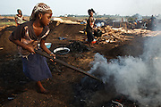 A girl uses a hoe to spread burning charcoal at a wood charcoal production site on the outskirts of San Pedro, Bas-Sassandra region, Côte d'Ivoire on Sunday March 4, 2012. Men, women and children - who don't go to school - work here seven days a week.
