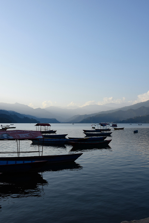 Boats on lake in front of the mountains at sunset with mist amongst the hills in Pewa, Pokhara, Nepal