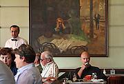 """Gäste im berühmten Kaffeehaus SLAVIA in der Prager Innenstadt. Im Hintergrund das Gemälde """"Der Absinthtrinker"""" von Maler Viktor Oliva.<br /> <br /> Visitors at the famous Café Slavia in the city centre of Prague. In the back a painting by Viktor Oliva with the title the Absinth drinker."""