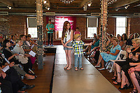Stevie Poehler patiently waits as Connor Hough enjoys an extra moment in the spotlight during the Fashion and Flair Show at the Belknap Mill on Sunday afternoon.  (Karen Bobotas/for the Laconia Daily Sun)