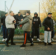 A group of bored lads sitting and standing outside by a wire fence