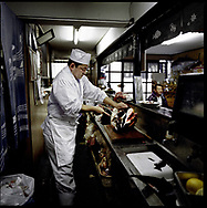 """Chef at a local tuna restaurant prepares the head of a blue fin tuna for a recipe called """"kabuto"""" (samurai helmet), Katsuura, Kii Peninsula, Japan.   Japan is known for having some of the richest fisheries in the world feed by the sub-tropical, Kurashio Current from the south which meets the sub-arctic, Oyashio Current mixing their nutrients off the coast of Fukushima Prefecture.  Climate change warming of seas will change this dynamic and a WWF reports suggests that fish species long associated with particular seasons may decline and it's possible some species will become extinct.  Katsuura, Wakayama Prefecture, Japan"""