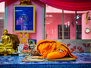 "29 MARCH 2017 - BANG KRUAI, NONTHABURI, THAILAND: A Buddhist monk leads a prayer during a ""Resurrection Ceremony"" at Wat Ta Kien (also spelled Wat Tahkian), a Buddhist temple in the suburbs of Bangkok. People go to the temple to participate in a ""Resurrection Ceremony."" Groups of people meet and pray with the temple's Buddhist monks. Then they lie in coffins, the monks pull a pink sheet over them, symbolizing their ritualistic death. The sheet is then pulled back, and people sit up in the coffin, symbolizing their ritualist rebirth. The ceremony is supposed to expunge bad karma and bad luck from a person's life and also get people used to the idea of the inevitability of death. Most times, one person lays in one coffin, but there is family sized coffin that can accommodate up to six people. The temple has been doing the resurrection ceremonies for about nine years.          PHOTO BY JACK KURTZ"