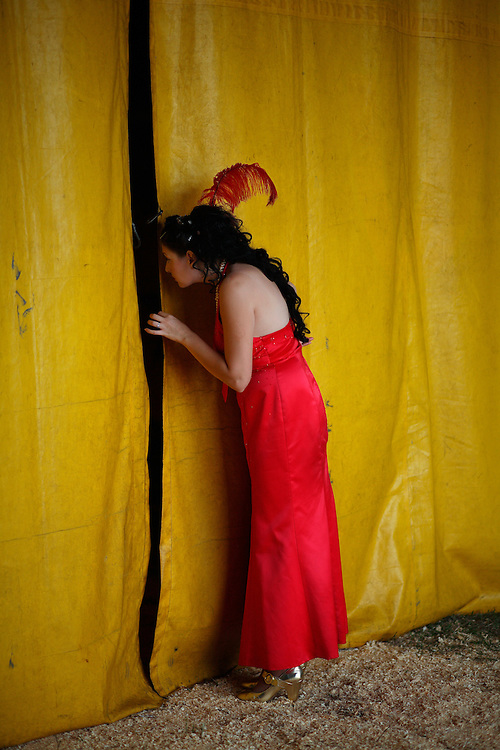 The Mistress of Ceremonies watches inside the tent from behind curtains at the Cole Brother Circus in Wilmington, North Carolina.