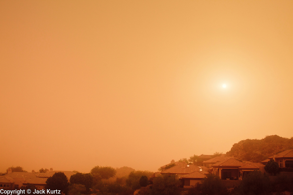 """18 AUGUST 2011 - PHOENIX, AZ:    Dust from a """"haboob"""" blots out the sun over a residential section of Phoenix Thursday. A haboob (Arabic for """"strong wind"""") is a type of intense duststorm commonly observed in arid regions throughout the world. They have been observed in the Sahara desert, the Arabian Peninsula, throughout Kuwait, and most arid regions of Iraq. In the USA, they are frequently observed in the deserts of Arizona, including Yuma and Phoenix, as well as New Mexico and Texas. """"Haboob"""" has been widely used to describe dust storms for more than a generation In Arizona but this year the very word """"haboob"""" has become a political football because some conservatives have lobbied against use of the word, favoring English words, like """"dust storm.""""    PHOTO BY JACK KURTZ"""