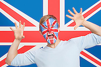 Portrait of young man with face painting screaming against British flag