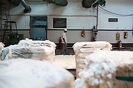 A worker works with raw cotton being processed using a machine in the Blow Room of the Pratibha vertically integrated garment unit in Indore, Madhya Pradesh, India on 11 November 2014. Photo by Suzanne Lee for Fairtrade