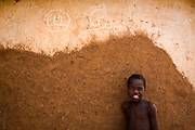 A child stands by a wall that has been marked with chalk to indicate that children in the house have been vaccinated in the village of Wantugu, northern Ghana, during a national polio immunization exercise on Friday March 27, 2009.