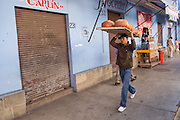A worker carries trays of Pan de Muerto a special sweet bread for celebrating the Day of the Dead festival at Central de Abastos Market October 28, 2014 in Oaxaca, Mexico.