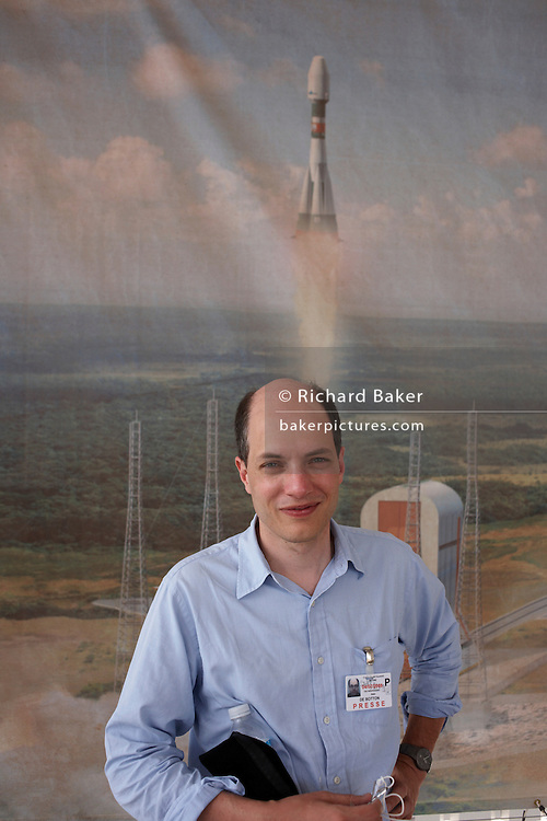 The writer, essayist and philosopher Alain de Botton stands in front of a mural of a Soyuz rocket of the Russian Federal Space Agency (Roskosmos) taking off from a mobile gantry at the European Space Agency (ESA). De Botton is in French Guiana researching his book 'The Pleasures and Sorrows of Work' published in April 2009. The illustration celebrates a future Russian mission if construction of their new facilities continues with the help of the French and other space agencies. Cosmonauts and technicians will ooccupy a purpose-built town near ESA's rocket complex. Alain de Botton (born Zurich, 1969) now lives in London. His best-selling books refer both to his own experiences and ideas- and those of artists, philosophers and thinkers. It's a style of writing that has been termed a 'philosophy of everyday life.'