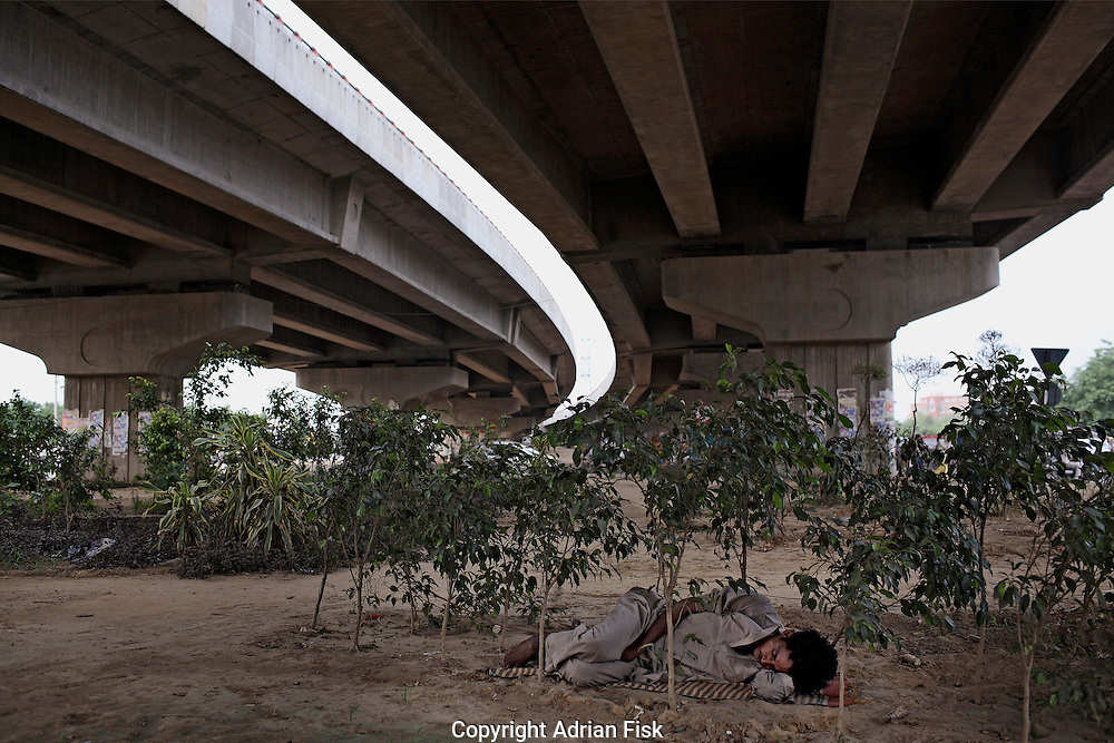 Gurgaon, Haryana State..Under a newly developed flyover linking New Delhi to the satellite town of Gurgaon a man finds somewhere to sleep.