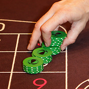 NLD/Schveningen/20120307 - Heropening Holland Casino Scheveningen, croupier plaatst waarde fiches op de tafel