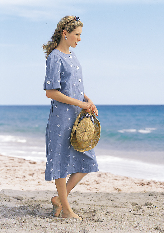 Photograph of a yong lady enjoying her vacation at the beach, while she is wearing a light blue summer dress and a straw hat.
