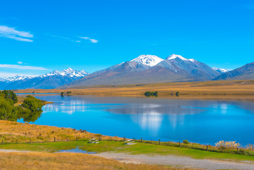 A quiet and peaceful lake with snowcapped mountains in the background.
