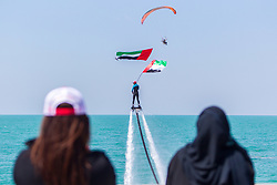 March 5, 2019 - Ras Al Khaimah, Ras Al Khaimah, United Arab Emirates - An Emirati lady and a local female resident are seen looking on as the jet pack and paraglider perform over Al Marjan Island as part of the Special Olympics Law Enforcement Torch Run celebration..The Special Olympics World Games 2019 will be hosted in Abu Dhabi, United Arab Emirates in March 2019 for the first time in the Middle East and North Africa since the movement's founding over 50 years ago. The final stage of the Special Olympics Law Enforcement Torch Run was held on Al Marjan Island, Ras Al Khaimah. The event was celebrated with traditional Emirati music and dances. The CEO of Marjan and Master Developer of Ras Al Khaimah, Mr Abdulla Al Abdouli opened the event. (Credit Image: © Mike Hook/SOPA Images via ZUMA Wire)