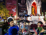 18 FEBRUARY 2016 - BANGKOK, THAILAND: People light their incense before praying at the Trimurti Shrine in Bangkok. Every Thursday night, starting just after sunset and peaking at 21.30, hundreds of Bangkok single people, or couples seeking guidance and validation, come to the Trimurti Shrine at the northeast corner of Central World, a large Bangkok shopping mall, to pray to Lord Trimurti, who represents the trinity of Hindu gods - Brahma, Vishnu and Shiva. Worshippers normally bring an offering of red flowers, fruits, one red candle and nine incense sticks. It's believed that Lord Trimurti descends from the heavens at 21.30 on Thursday to listen to people's prayers. Although most Thais are Buddhists, several Hindu traditions have been incorporated into modern Thai Buddhism, including reverance for Trimurti.       PHOTO BY JACK KURTZ