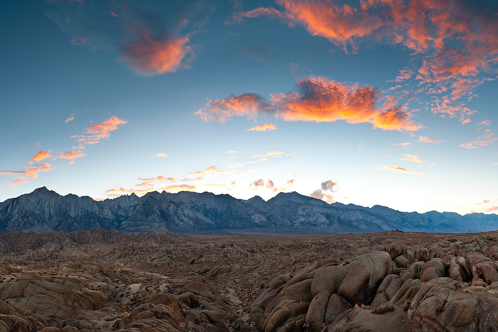 Alabama Hills, Whitney Portal, CA.   As the day began to end, I searched for closure from it in the Alabama Hills, a jumble of desert and rocks heaved up and tilted sideways by earthquakes, baked by the sun, and sculpted by erosion.  Outside of Lone Pine, on the Whitney Portal Road, it is a chaotic interlude between the gentle valley below and the solid granite wall that stretches northward. At the skyline, the Sierra serrate the blue, and the wind drives fire clouds overhead and tears them apart.  I can see the portal road like a flying V switchbacking up the rock, where it will culminate as the gateway to climb the highest mountain in the lower 48.  Walking across that threshold is to enter a mountain wonderland of tarns, cirques, boulder fields, endlessly interesting forest, and ever salivating views.  But portals are everywhere, aren't they?  I must have passed through one on the road into this complicated world, underneath the Sierra.  It's an entrance that I chase through, or maybe an exit I am chased from--I could make a case for either. I suppose the camera is even a passageway in my hands, an instrument by which I frame and define what I'm looking for.  And what am I looking for?  Knowledge.  Confidence.  A clear vision.  An unwavering heart.  How seldom I find it...how seldom I'm found. I drop my weight at the door for awhile, to concentrate on the event of color and detail dissolving into the twilight. And eventually come back, the door opens both ways.