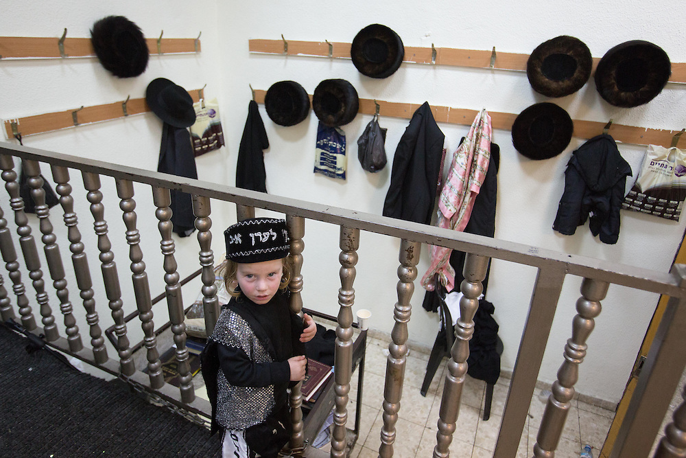 An Ultra-orthodox boy dressed in costume stands at the Matmidim Hasidic dynasty synagogue, during Purim tish. Jerusalem, Israel, 25 February 2013. Photo by Oren Nahshon.