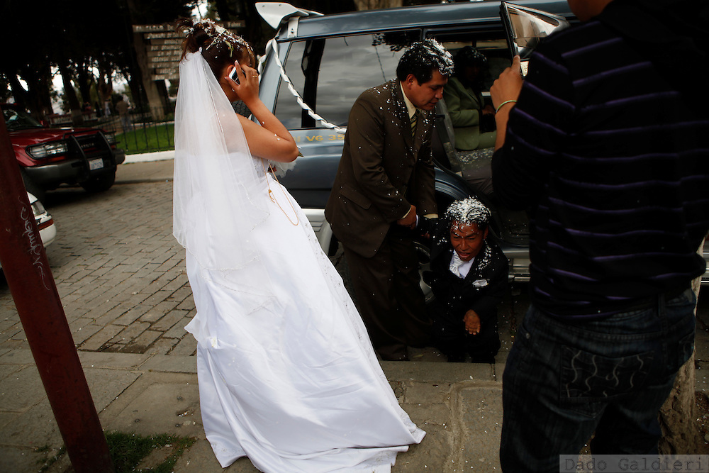 Cresencio Choque is helped by a godfatherto leave an SUV as his wife  Ysabel, left, speaks on the phone after getting  married in the city of La Paz, Saturday, Dec. 19, 2009